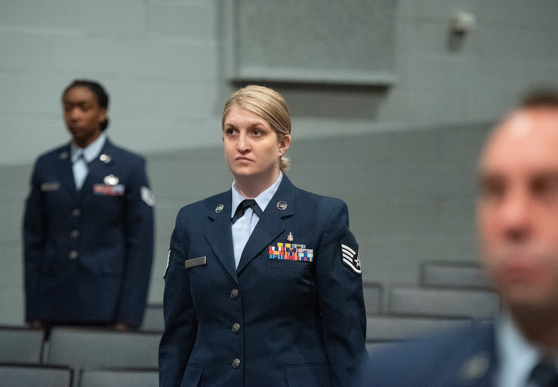 Staff Sgt. Victoria Daniels, U.S. Air Force School of Aerospace Medicine, stands with classmates as their degrees are conferred during the Community College of the Air Force spring graduation ceremony May 26, 2021, in the theater at Wright-Patterson Air Force Base, Ohio. Daniels earned an associate's degree in instruction of technology and military science. (U.S. Air Force photo by R.J. Oriez)