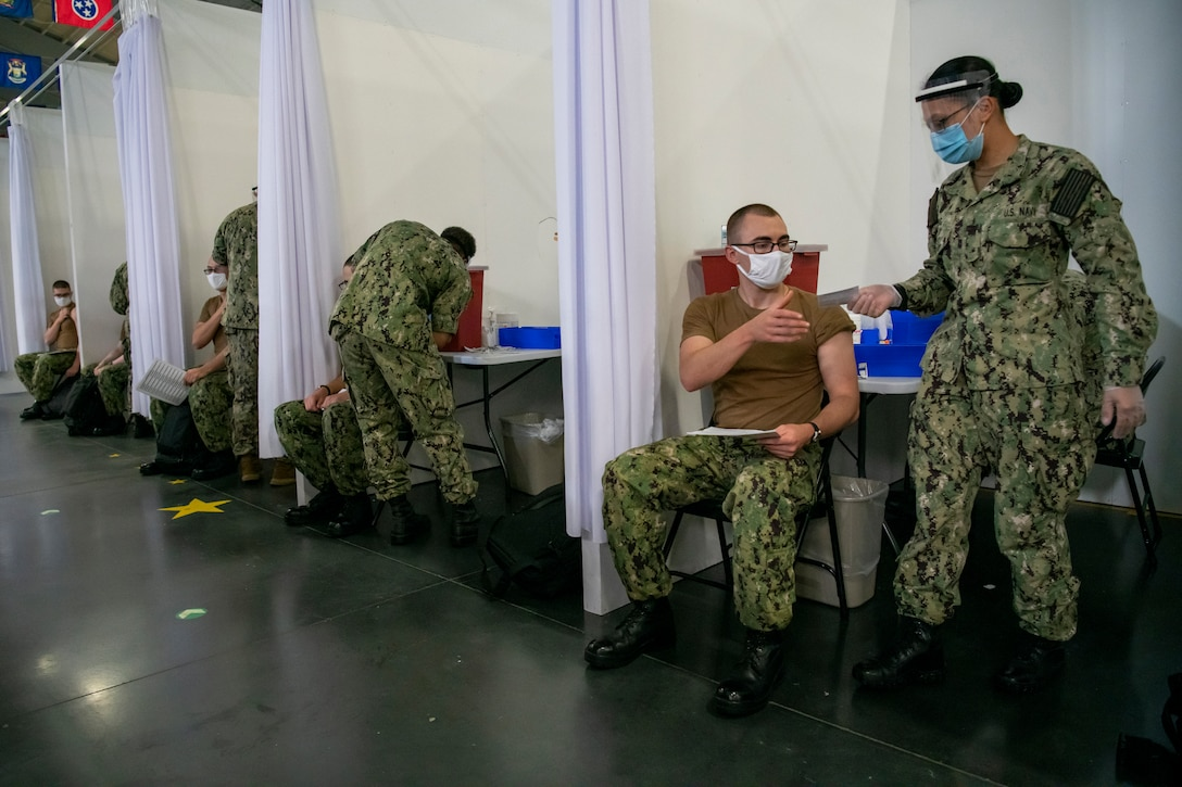 Inside a row of cubicles, a service member wearing a face mask and gloves hands a paper to a young service member who is seated and wearing a face mask. Similar activities are going on inside four other cubicles.
