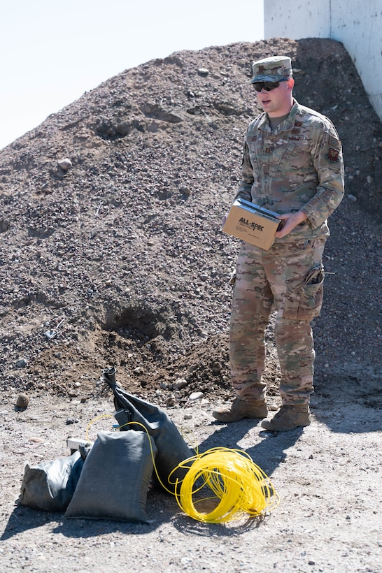 Capt. William Knox, 341st Civil Engineer Squadron explosive ordnance disposal flight commander, explains how a remote-fired shotgun fired a hole through a cardboard box during a training demonstration June 2, 2021, at Malmstrom Air Force Base, Mont.