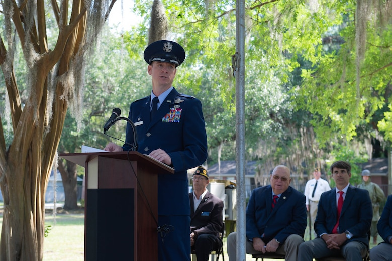 A photo of the 23d Wing commander speaking at a podium