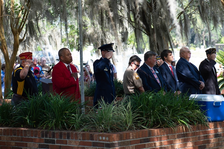 A photo of attendees paying respects during taps.