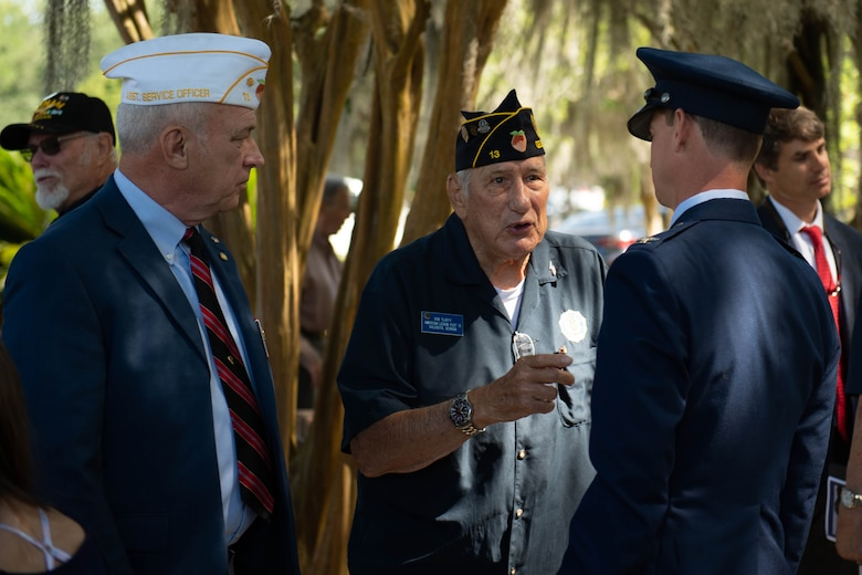 A photo of an Airman speaking to veterans.