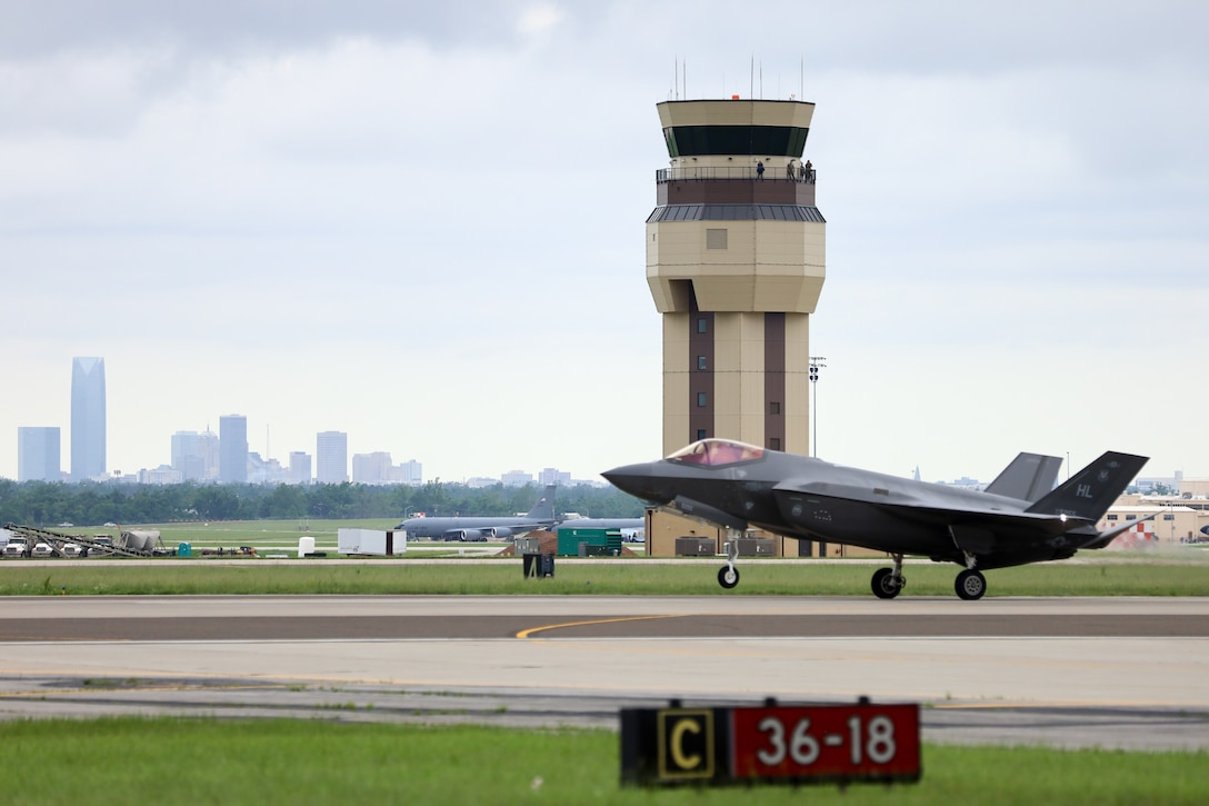 Airplane with air traffic control tower and downtown skyline in the background
