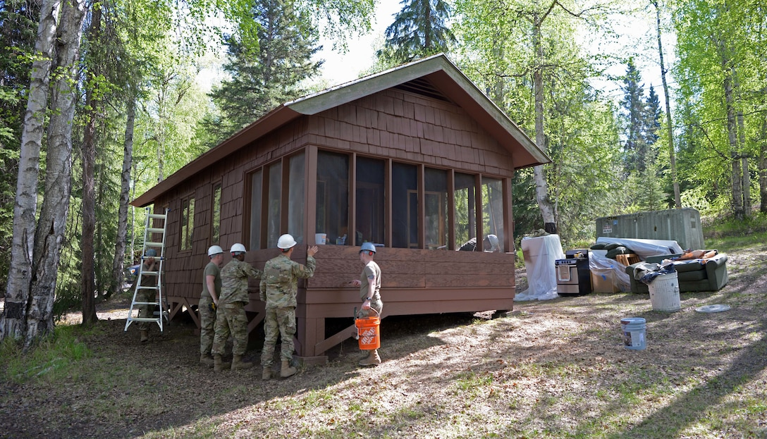 U.S. Air Force Airmen from the 354th Civil Engineer Squadron renovate a cabin during a troop training project May 26, 2021, at the Birch Lake Military Recreation Area, Alaska. Troop training projects are a multi-craft annual readiness requirement for members of civil engineer squadrons that allow them to work together to construct a high quality product in a simulated contingency environment. (U.S. Air Force photo by Senior Airman Beaux Hebert)