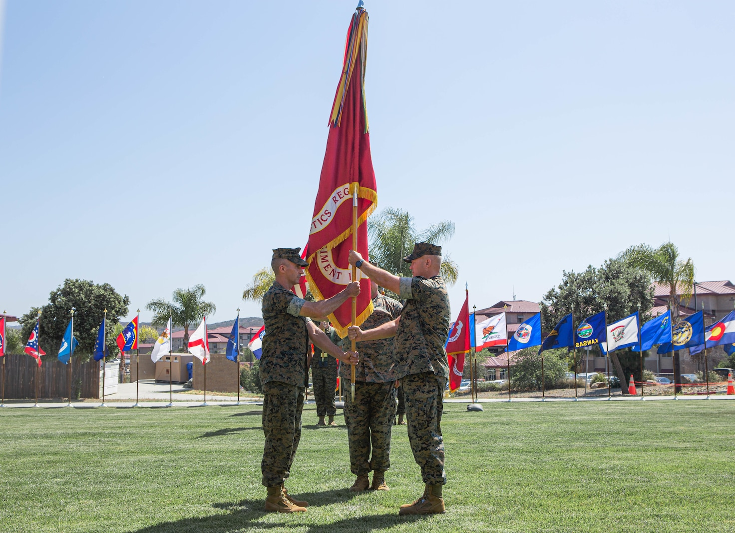 U.S. Marine Corps Col. Michael W. Stehle, outgoing commanding officer, right, Combat Logistics Regiment 1, 1st Marine Logistics Group, and incoming commanding officer Col. Ryan E. Scott, left, exchange the Regimental colors during the CLR-1 change of command ceremony.