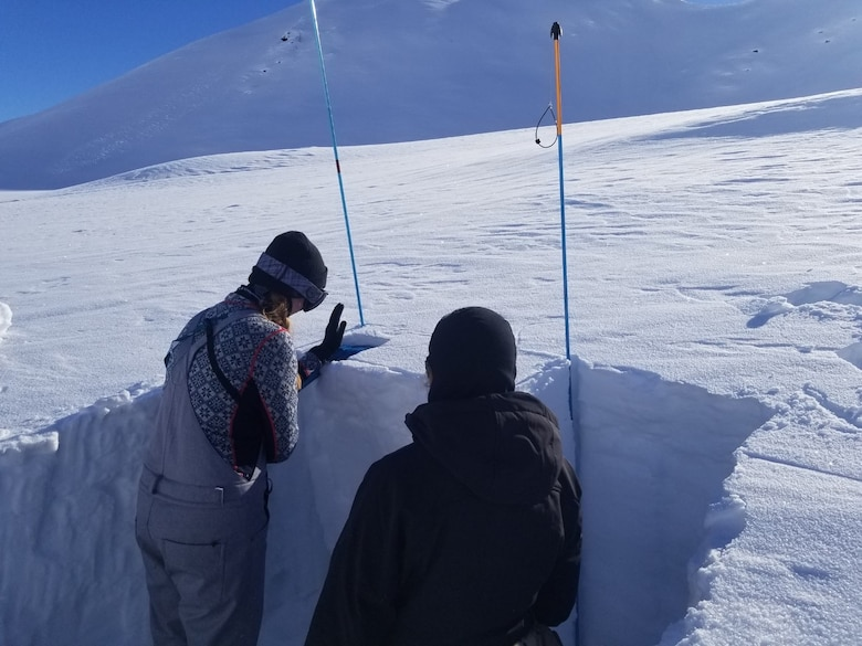Capt. Lynsie Schwerer, Officer In Charge, Brigade Weather Operations, assigned to Detachment 3, 1st Combat Weather Squadron, Joint Base Elmendorf-Richardson, Alaska, performs a snow depth measurement during Arctic Survival Training. (Courtesy photo)