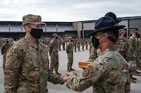A trainee receives an Airmen's coin from a Military Training Instructor.