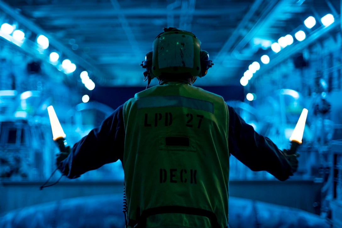 A U.S. Sailor assigned to amphibious transport dock USS Portland, signals Landing Craft, Air Cushion 72, with Assault Craft Unit 5, to depart the well deck for an amphibious raid exercise, May 17, 2021. Marines and Sailors of the 11th Marine Expeditionary Unit and the Essex Amphibious Ready Group are conducting integrated training off the coast of southern California.