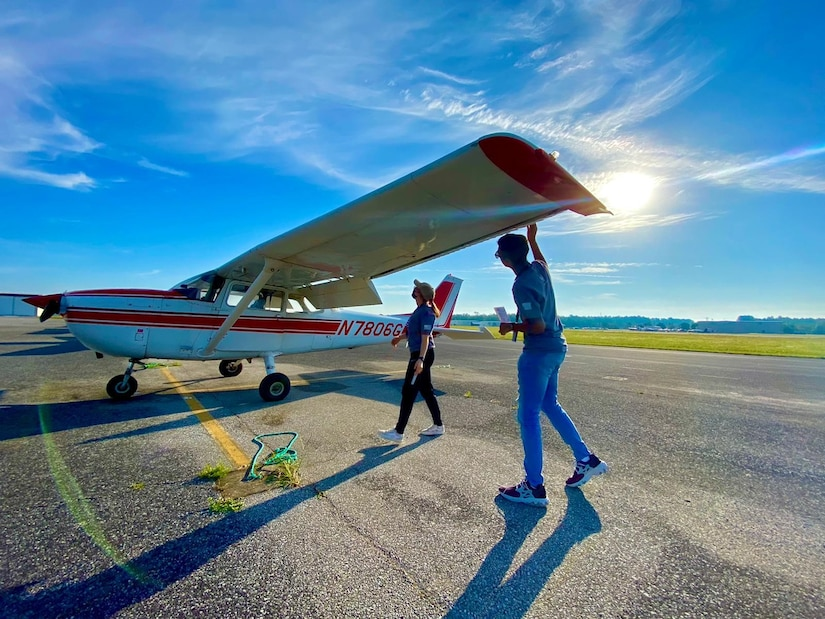 Two people check a small aircraft before a flight.