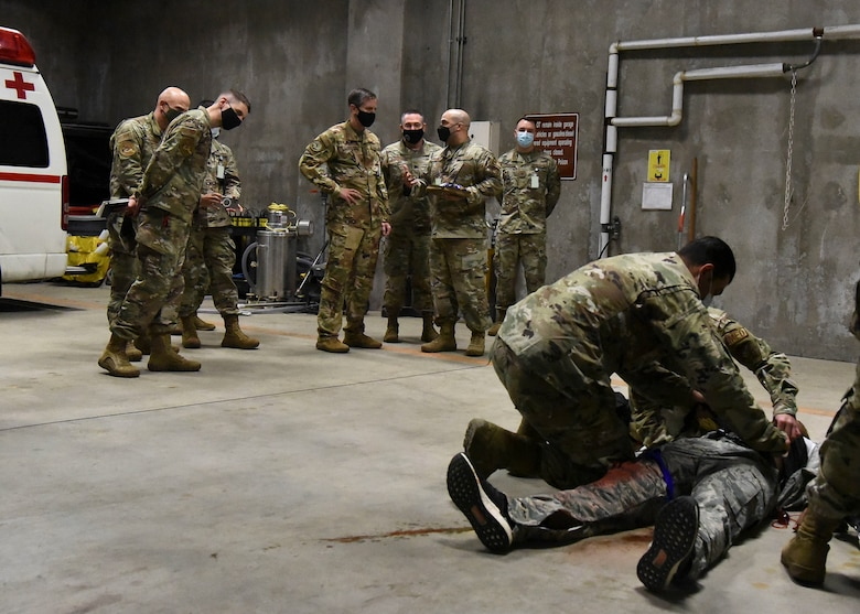 Military members work on an acting victim in front of an audience of military members.