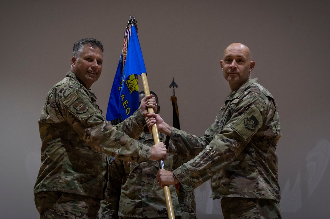 two people stand on stage holding a guidon.