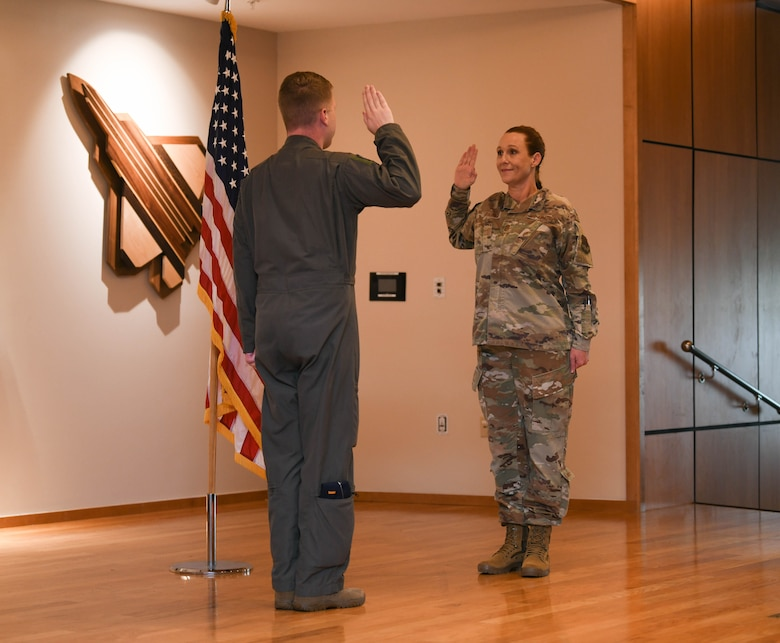 Grabham and Garcia hold their right hands up during the oath of enlistment