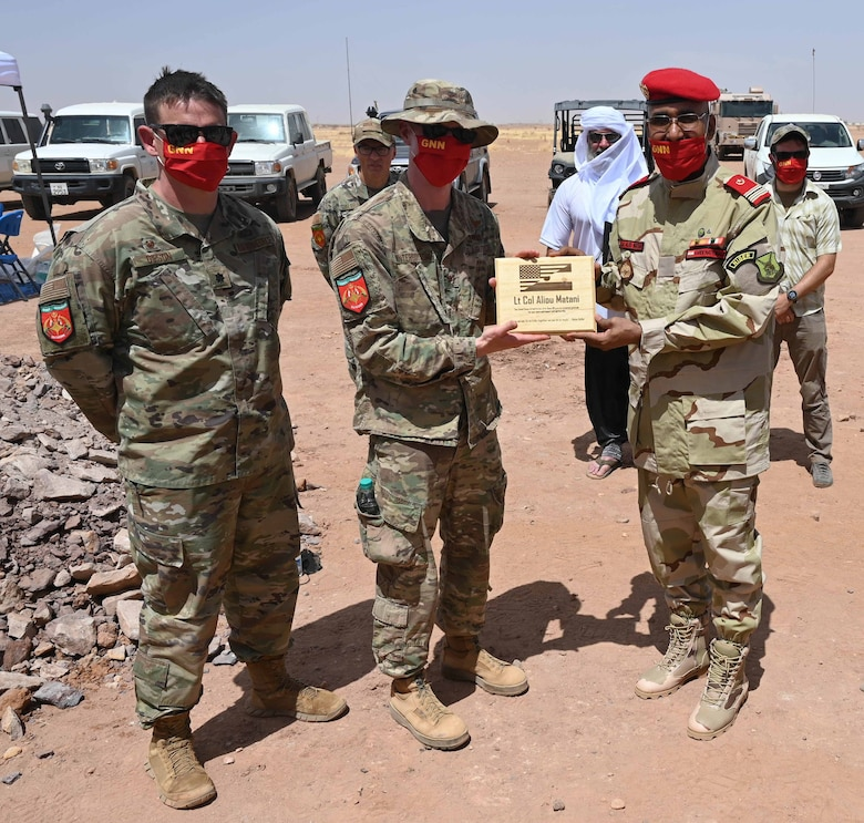 Col. Winterbottom and Lt. Col. Gipson (left) present a gift of appreciation to Nigerien National Guard Lt. Col. Aliou Matani at Nigerien Air Base 201, Agadez, Niger, May 31, 2021. Since 1990, the U.S. has provided $25 million dollars to help partnerships flourish in areas of law enforcement, border security, and civilian safety through counter-terrorism exchanges and equipment donation.