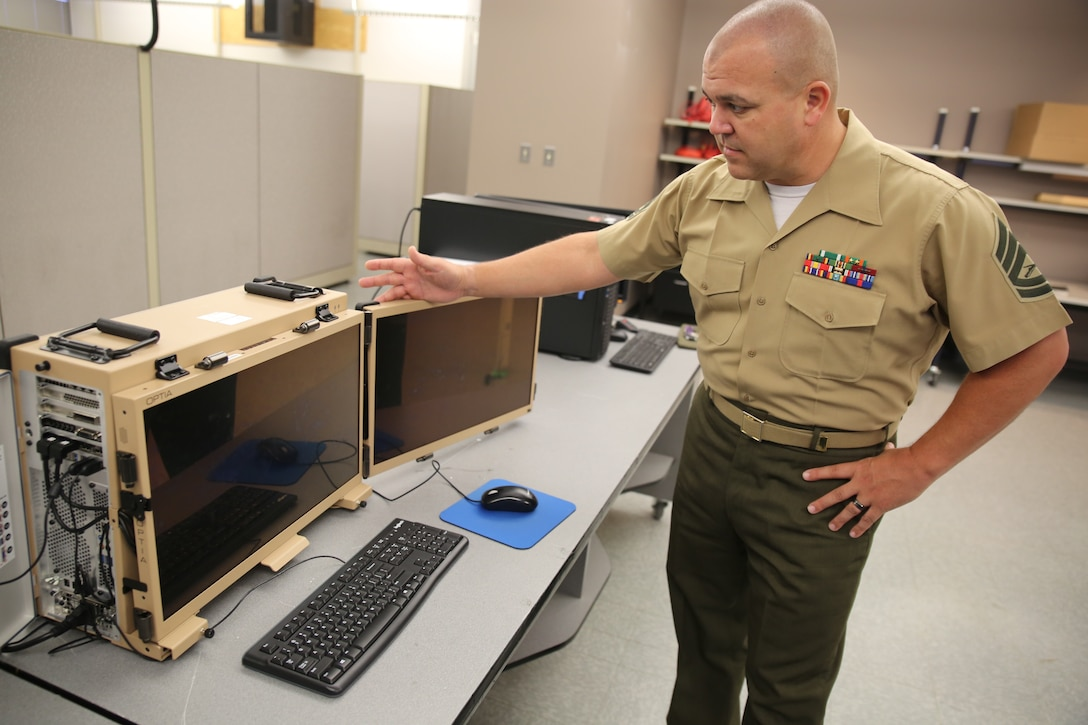 Gunnery Sgt. Travis Godley, a subject matter expert at Marine Corps Systems Command, showcases the modernized Distributed Common Ground System-Marine Corps workstation, May 21, 2021, in Stafford, VA. The recently fielded, upgraded DCGS-MC is a mobile, secure and integrated intelligence system that Intel Marines can leverage to inform commanders of threats on the battlefield
