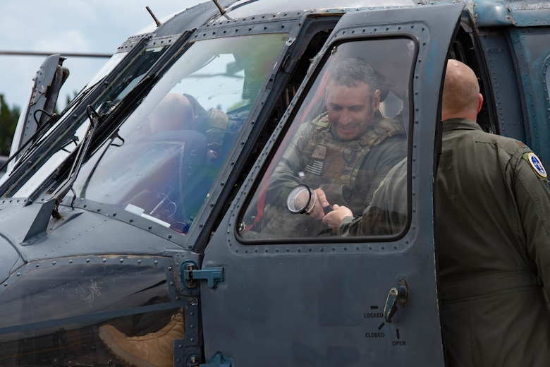 A photo of an Airman getting out of a helicopter.