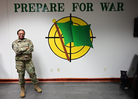 An airman stands in front of a wall with the text 'prepare for war' and a green flag logo.
