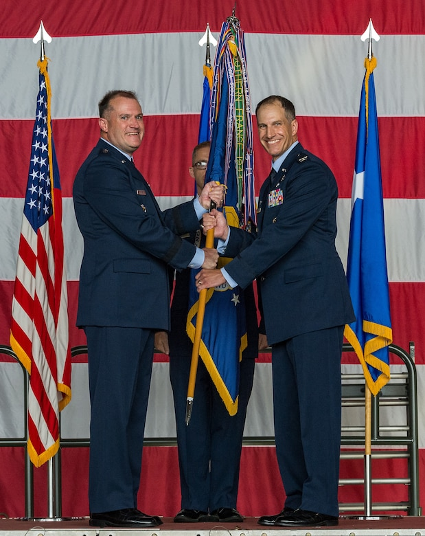 Maj. Gen. Thad Bibb, left, 18th Air Force commander, presents the 436th Airlift Wing guidon to Col. Matthew Husemann, 436th AW commander, during an assumption of command ceremony on Dover Air Force Base, Delaware, June 4, 2021. Upon taking command, Husemann became the wing's 36th commander. (U.S. Air Force photo by Roland Balik)
