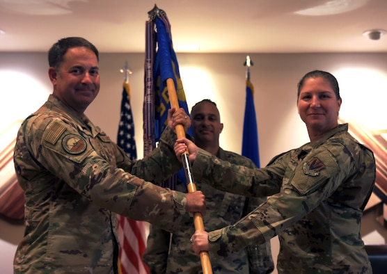 Two people hold a guidon