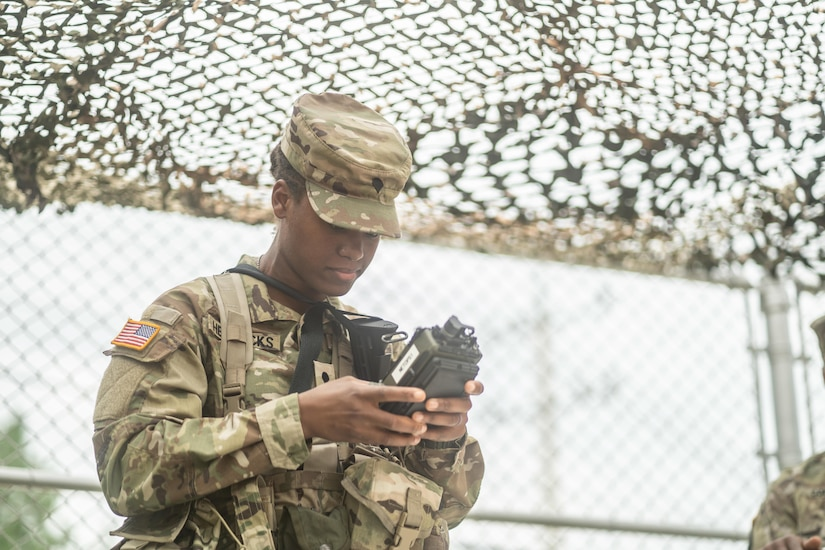 A woman dressed in a military uniform operates a radio.