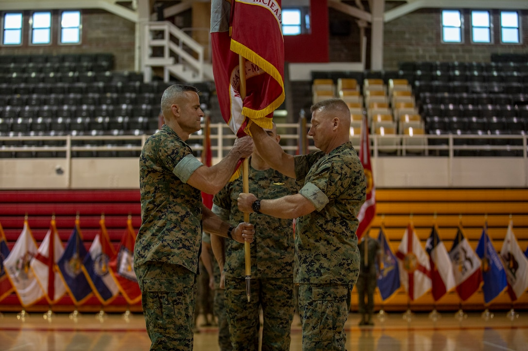 U.S. Marine Corps Maj. Gen. Julian D. Alford, right, outgoing commanding general, Marine Corps Installations East-Marine Corps Base Camp Lejeune, passes the organizational colors to Brig. Gen. Andrew M. Niebel, right, incoming commanding general for MCIEAST-MCB Camp Lejeune, during the change of command ceremony on MCB Camp Lejeune, North Carolina, June 4, 2021. (U.S. Marine Corps photo by Lance Cpl. Isaiah Gomez)