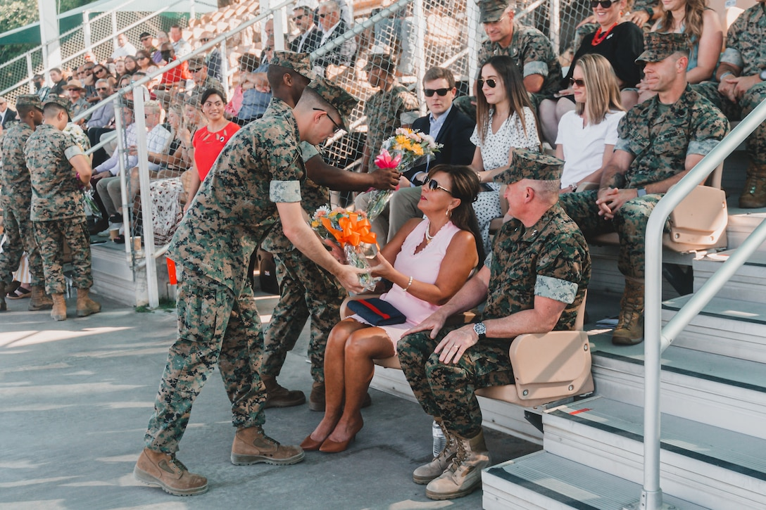 A U.S. Marine presents flowers to Sue Jurney, spouse of U.S. Marine Corps Maj. Gen. William M. Jurney, during the Marine Air Ground Task Force Training Command, Marine Corps Air Ground Combat Center change of command ceremony on June 4, 2021. During the ceremony, Jurney relinquished command to Maj. Gen. Austin E. Renforth. (U.S. Marine Corps photo by Lance Cpl. Colton Brownlee)