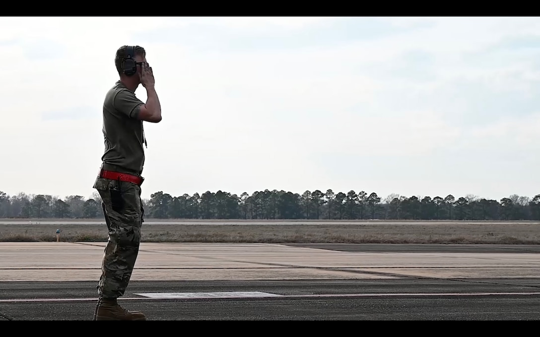 man salutes and aircraft before it departs