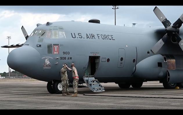 two airmen share a high five next to an aircraft