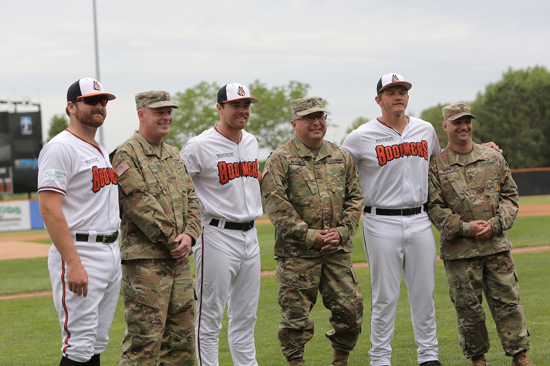 Soldiers assigned to the 85th U.S. Army Reserve Support Command headquarters pause for a photo with players from the Schaumburg Boomers baseball team, May 31, 2021, in Schaumburg, Illinois during a Memorial Day home game against the Gateway Grizzlies.