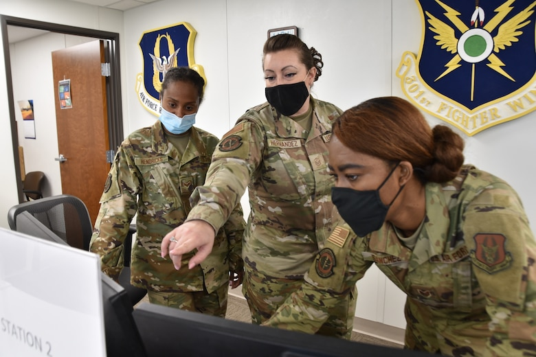 (center) 301st Fighter Wing Force Support Squadron and Wing Staff Agency first sergeant, Master Sgt. Cassandra Hernandez interacts with FSS personalists, Senior Airman Hendricks and Staff Sgt. Sanchez as they show her a new system at U.S. Naval Air Station Joint Reserve Base Fort Worth, Texas on June 5th, 2021. The first sergeant's primary role is to support the mission through interaction, support and management of all unit-assigned personnel and their families. (U.S. Air Force photo by Senior Airman William Downs)