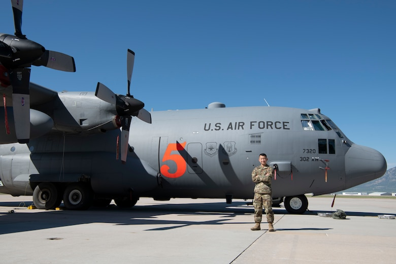 Airman stands in front of C-130
