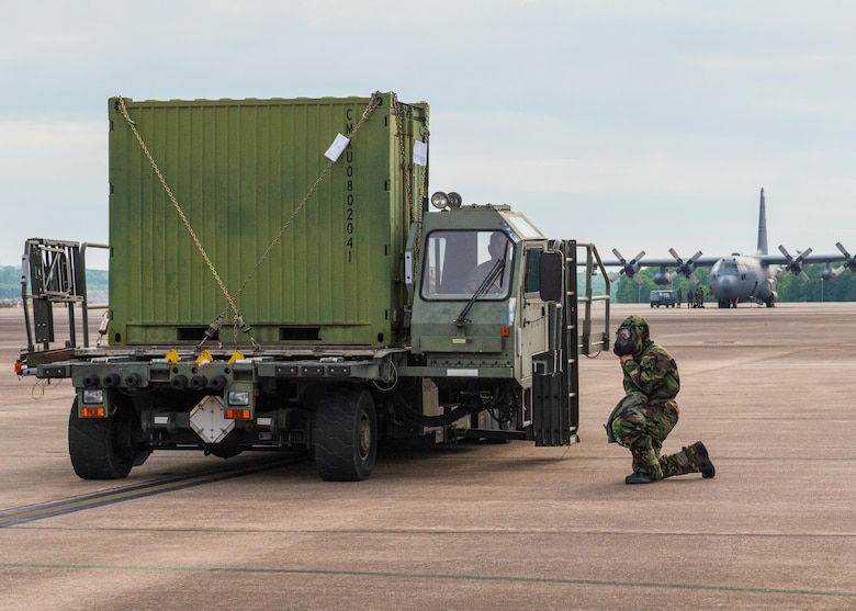 An Airman spots and guides large equipment being loaded onto aircraft while in personal protective equipment at Little Rock Air Force Base, Arkansas, June 5, 2021. 'Port Dawgs' from the 189th Aerial Port Flight, Air National Guard, and from the 96th Aerial Port Squadron, Air Force Reserve, created a joint training event focused on aerial port operations at Little Rock Air Force Base, Arkansas, June 3-6, 2021. (U.S. Air Force photo by Senior Airman Julia Ford)