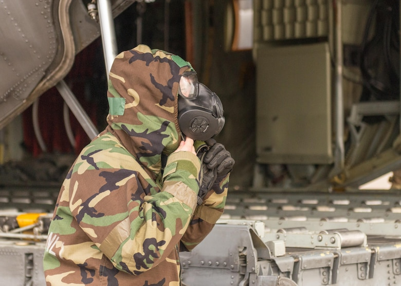 An Airman adjusts his gas mask and personal protective equipment at Little Rock Air Force Base, Arkansas, June 5, 2021. 'Port Dawgs' from the 189th Aerial Port Flight, Air National Guard, and from the 96th Aerial Port Squadron, Air Force Reserve, created a joint training event focused on aerial port operations at Little Rock Air Force Base, Arkansas, June 3-6, 2021. (U.S. Air Force photo by Senior Airman Julia Ford)