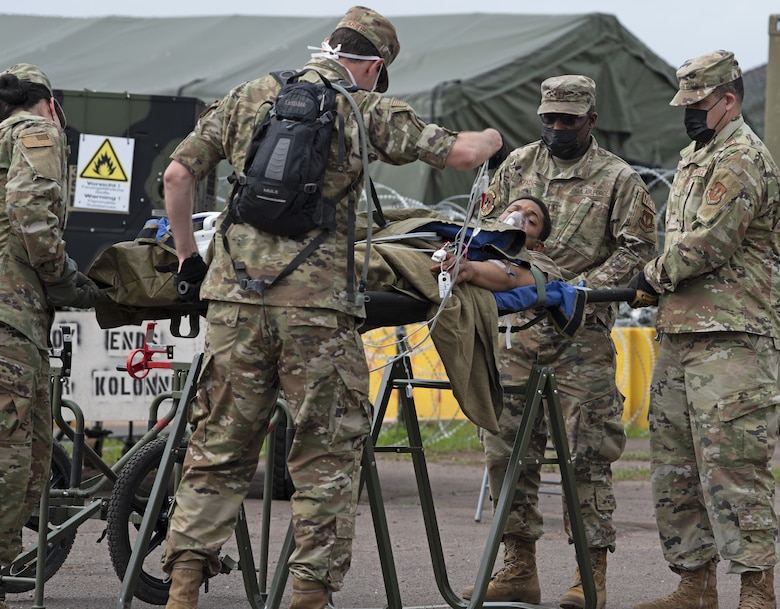52nd Medical Group Airmen attend to a simulated casualty during Saber Guardian 21 at Baumholder, Germany, June 3, 2021. The Airmen supported the exercise by providing rapid response en-route patient staging for Aeromedical Evacuation in support of contingency operations. (U.S. Air Force photo by Tech. Sgt. Tony Plyler)