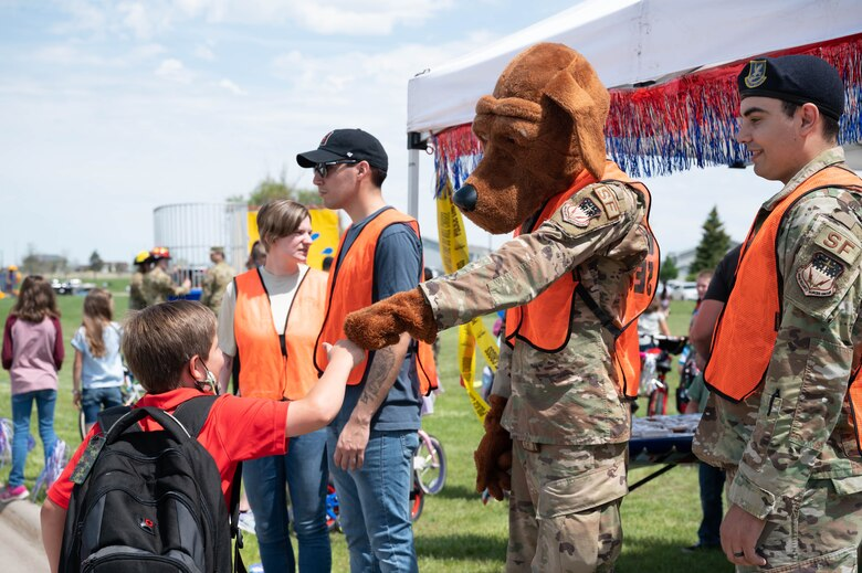 McGruff the crime dog fist bumps a military child during a bike safety rodeo June 4, 2021, at Malmstrom Air Force Base, Mont.