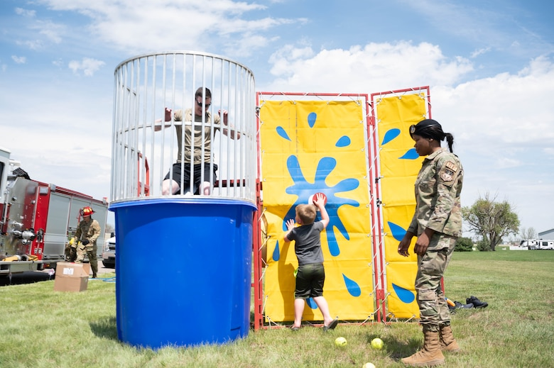 Maj. Derek Tosie, left, 341st Security Forces Squadron commander is dunked in a tank by Luke Elliott, center, son of Staff Sgt. Brandon Elliott, 741st Missile Security Forces Squadron field security controller, while Airman 1st Class Veasia Shavers, 341st SFS installation patrolman, watches June 4, 2021 at Malmstrom Air Force Base Mont.