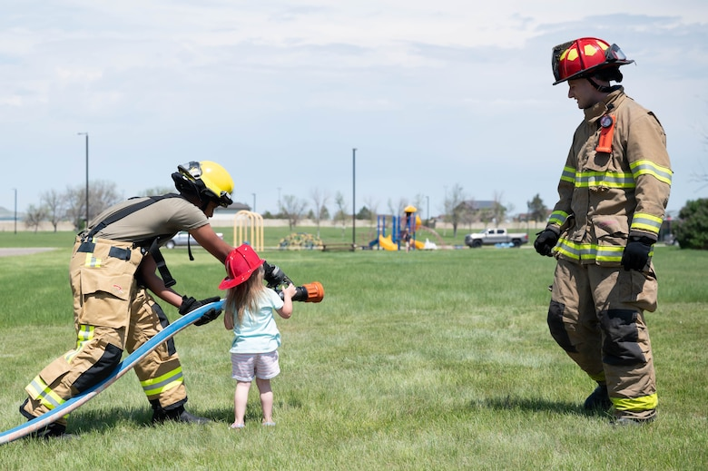 Airman 1st Class Nilton Pinto Depina, left, 341st Civil Engineer Squadron firefighter, demonstrates how to operate a fire hose during a bike safety rodeo June 4, 2021, at Malmstrom Air Force Base, Mont.
