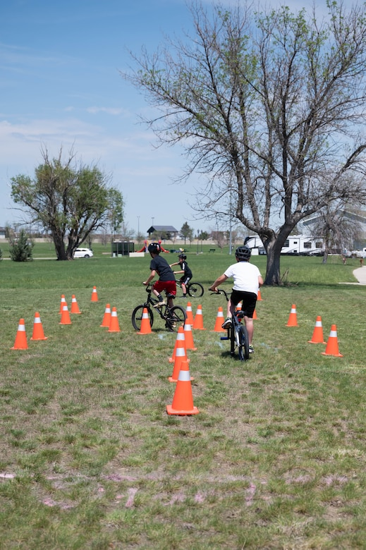 Military children ride bicycles through an obstacle course during a bike safety rodeo June 4, 2021, at Malmstrom Air Force Base, Mont.