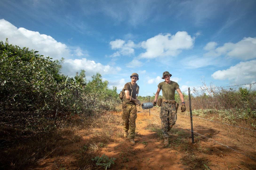 Australian Army Engineer Tyson Buckley and U.S. Marine Corps Lance Cpl. Deitrick McMahon, a combat engineer with Combat Logistics Battalion 7, Marine Rotational Force – Darwin, build a barbed wire fence during exercise Crocodile Response at Point Fawcett, NT, Australia, May 25, 2021. Exercise Crocodile Response tested the ability of MRF-D and the Australian Defence Force to provide disaster relief in the Indo-Pacific region. The rotational deployment of U.S. Marines affords a combined training opportunity with Australia and improves cooperation and integration between the two country's forces.