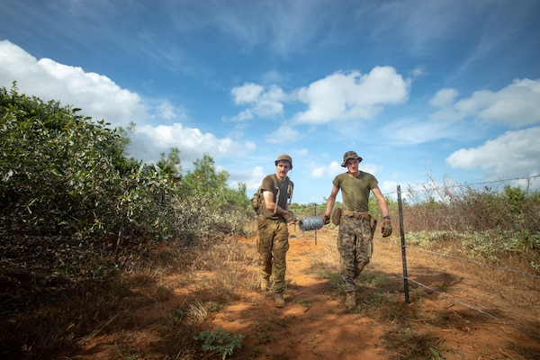 An Australian Army Engineer and U.S. Marine build a barbed wire fence during exercise Crocodile Response at Point Fawcett, NT, Australia, May 25.