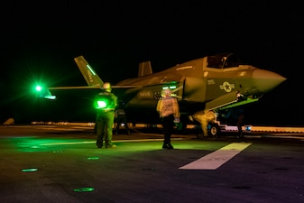 Sailors and Marines secure an F-35B Lightning aboard USS America (LHA 6).