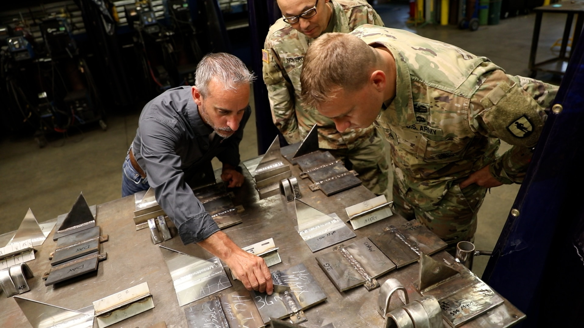 Eric Vannoy, lead welding instructor at Salina Area Technical College, left, inspects the work of Soldiers enrolled in the Advanced Leaders Course for the 91E Allied Trade Specialist military occupational specialty qualification course at the Kansas Army National Guard's Regional Training Site for Maintenance in Salina, Kansas, May 20, 2021. The KSARNG-SATC  partnership gives Soldiers completing the Army course the opportunity to enroll in and receive credit for college courses.