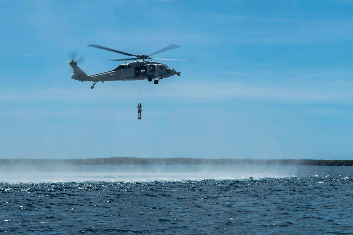 A  sailor holds on a rope attached to a helicopter hovering over a body of water.