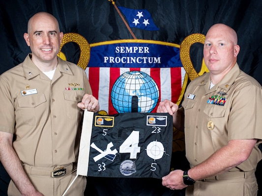 USS New Hampshire's commanding officer and chief of the boat display the boat's battle flag.