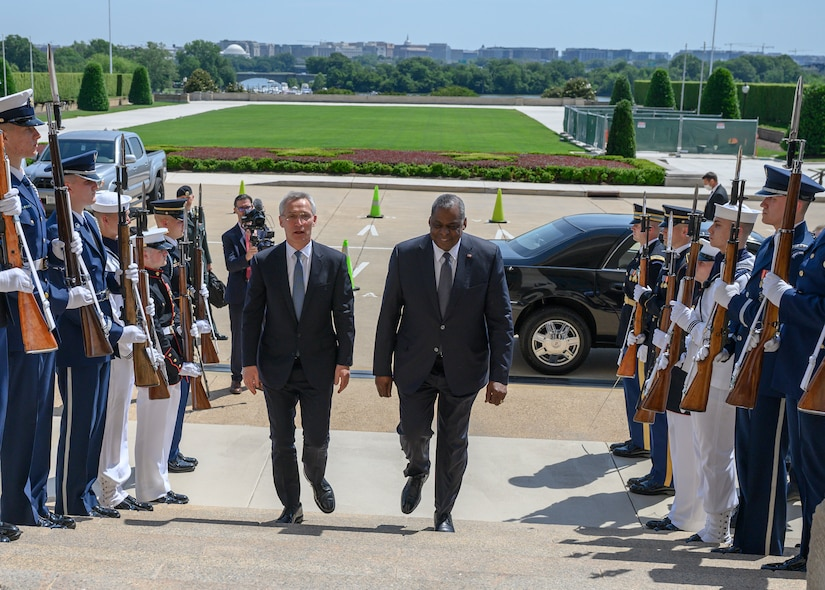 Two men in suits walk up stairs between rows of military service members.