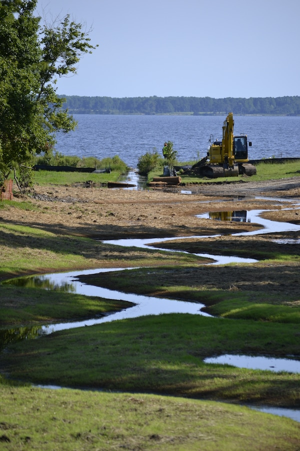 A stream in the process of being restored in the Grant's Landing residential housing area, filters water that runs off into the Neuse River at Marine Corps Air Station (MCAS) Cherry Point, North Carolina, July 29, 2015. The Environmental Affairs Department (EAD) responded to concrete lined ditched carrying contaminants to the Neuse River by removing the concrete ditches, restoring the natural curves in the streamline. They put down coconut fiber matting to give the banks steadiness for the planted shrubbery, grasslands and trees to filter water from the storm drains before making it to the streamline.  (U.S. Marine Corps Courtesy Photo by: Jessica Guilianelli)