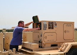 Mitchell D. Holt, a sensor logistics assistance representative at the Regional Support Center, Camp Arifjan, Kuwait, turns on a 10kw AMMPS generators on May 20.  Technicians at the 401st Army Field Support Brigade Communications-Electronics Command RSC recently attained the ability to rebuild 10kw AMMPS generators within the U.S. Central Command. The ability to rebuild generators locally is expected to save money while providing sustainable assists to Soldiers in the field.