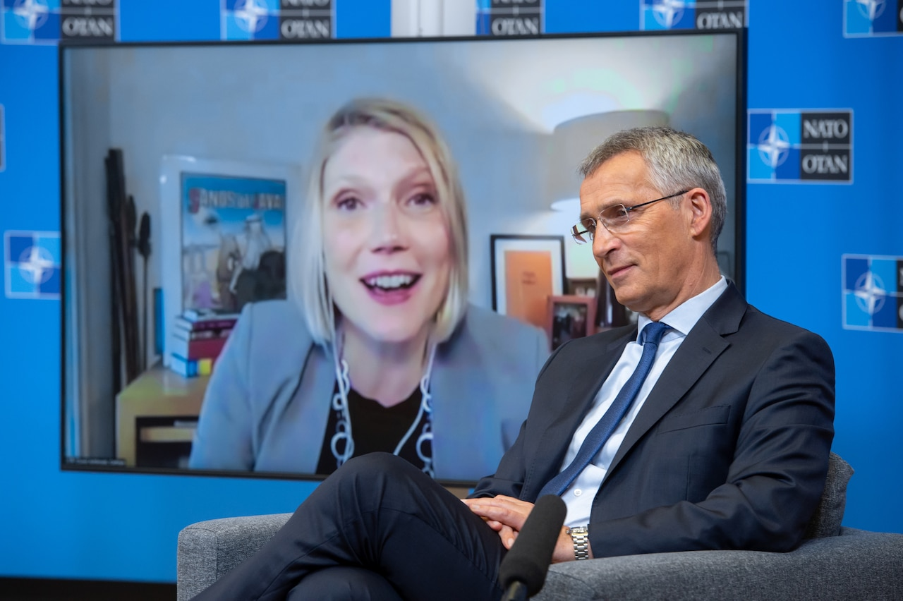 A man sits in a chair answering questions from a woman on a screen.