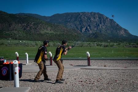 two men shoot at clay targets.