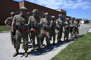 Eight military members hold large clear shields that have the word police on them as they train to maintain peace during civil unrest during a unit training assembly at the North Dakota Air National Guard Base, Fargo, N.D., June 5, 2021.