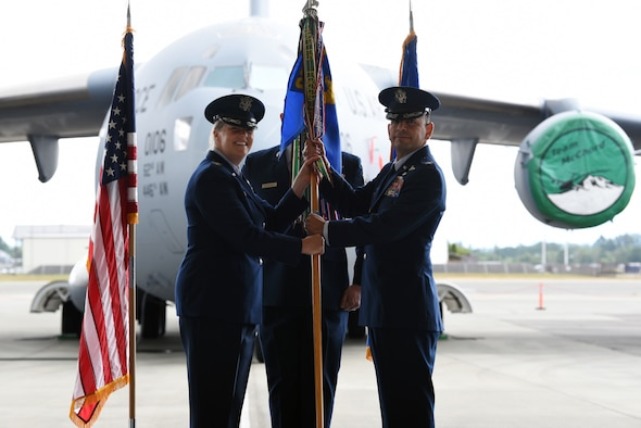 U.S. Air Force Col. Erin Staine-Pyne, 62nd Airlift Wing commander, presents the 62nd Operations Group guidon to Col. Sergio E. Anaya, the new 62nd OG commander, during the group's assumption of command ceremony at Joint Base Lewis-McChord, Washington, June 7, 2021. As the 62nd OG commander, Anaya ensures the combat readiness of three C-17A Globemaster III airlift squadrons and an operations support squadron to conduct all aspects of C-17 operations. Anaya is a senior pilot with more than 3,800 hours in the C-17 Globemaster III, C-21A, T-1 Jayhawk, and T-37 Tweet aircraft and has logged more than 930 combat hours. (U.S. Air Force photo by Senior Airman Zoe Thacker)